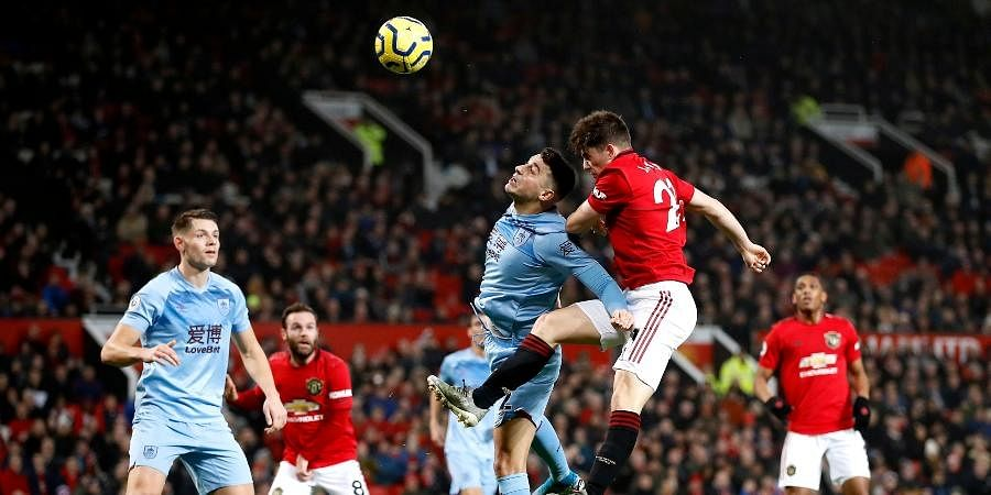 Burnley's Matthew Lowton, centre and Manchester United's Daniel James battle for the ball, during the English Premier League soccer match between Manchester United and Burnley, at Old Trafford, in Manchester.