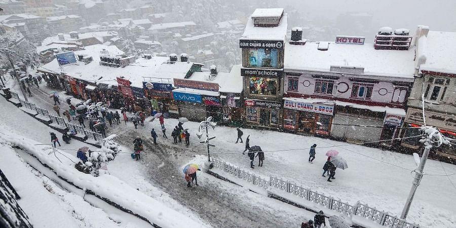 People walk on snow covered roads amid heavy snowfall in Shimla on Wednesday Jan. 8 2020. (Photo | PTI)