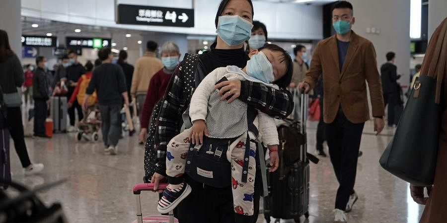 Passengers wearing protective face masks enter the departure hall of a high speed train station in Hong Kong