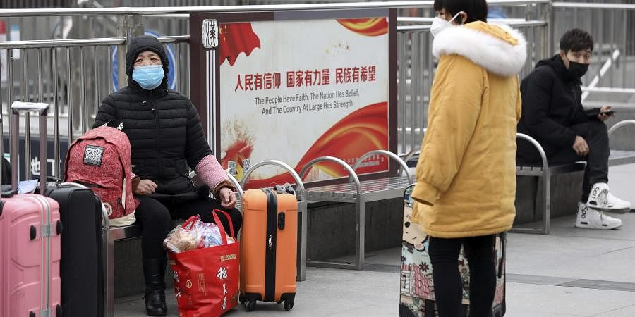 Travellers sit with their luggage outside the closed Hankou Railway Station in Wuhan in central China's Hubei Province