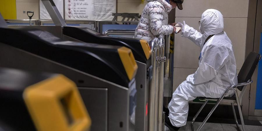 A worker wearing a hazardous materials suit gives directions to a passenger at a subway station in Beijing