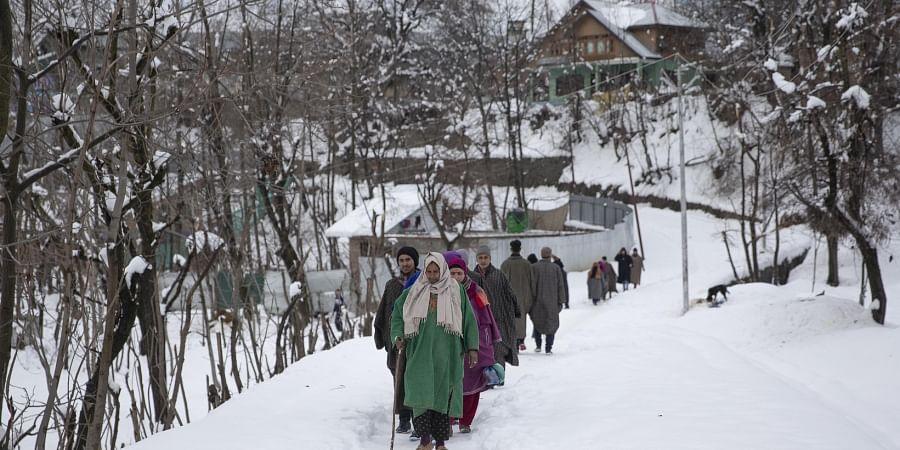 Kashmiri villagers walk through a snow covered road near Kangan village, north of Srinagar, Tuesday, Jan. 14, 2020. (Photo   AP)