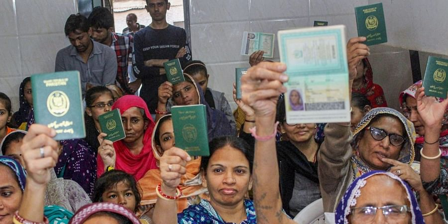 Hindu refugees who migrated from Sindh province of Pakistan display their passports as they support the Citizenship Amendment Act in Ahmadabad, Monday, Dec. 23, 2019.