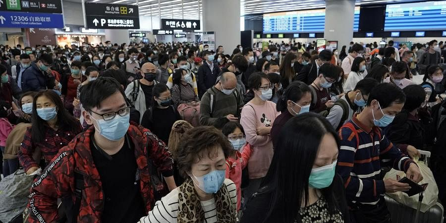Passengers wear protective face masks at the departure hall of the high speed train station in Hong Kong. Fear about the effects of a new virus found in China is spreading faster through financial markets around the world than the sickness itself.