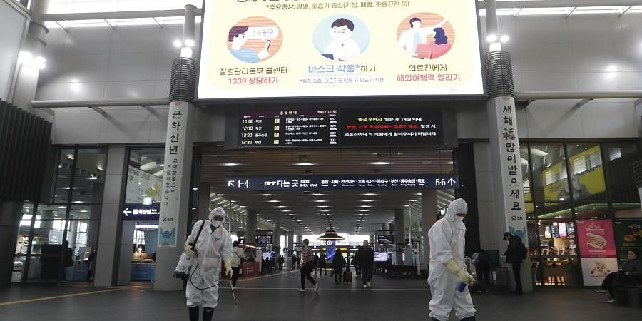 Employees work to prevent a new coronavirus as a screen warming about Wuhan coronavirus at Suseo Station in Seoul, South Korea, Friday, Jan. 24, 2020.