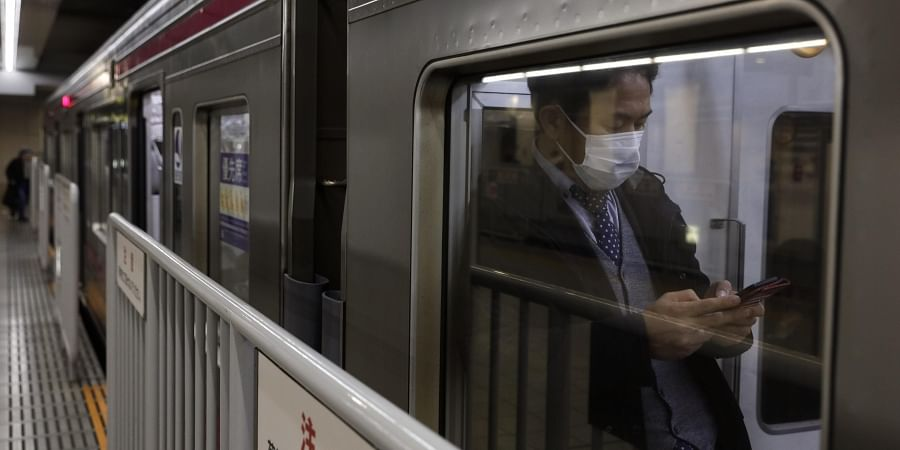 A commuter wearing a mask waits for a train to depart at Shinjuku Station in Tokyo, Monday, Jan. 27, 2020.