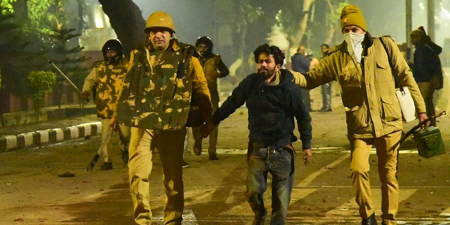Police take away a student after clashes following protests over Citizenship Amendment Act on the campus of Aligarh Muslim University