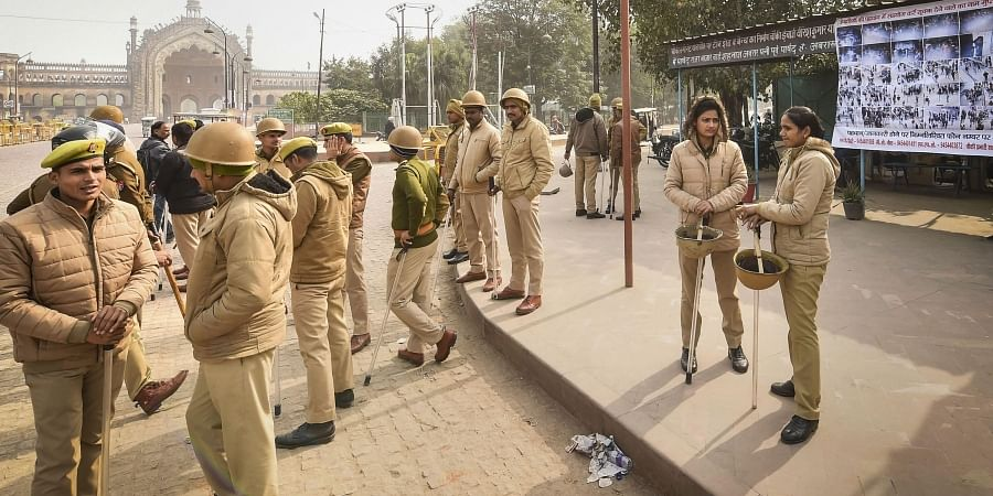 Police personnel stand guard beside a poster of protestors suspected to have incited vandalism during protests against CAA and NRC in Lucknow Friday