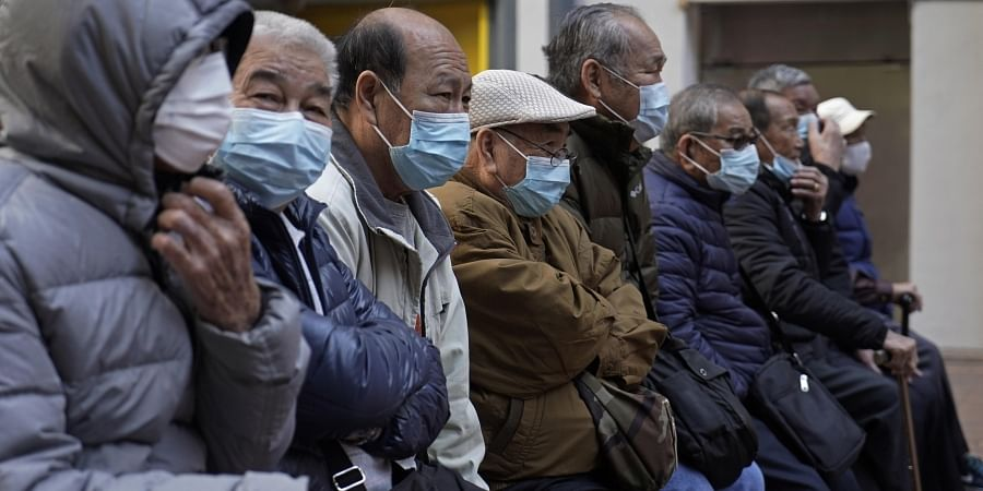 Elderly men sit at a park wearing face masks in Hong Kong, Thursday, Jan. 30, 2020.