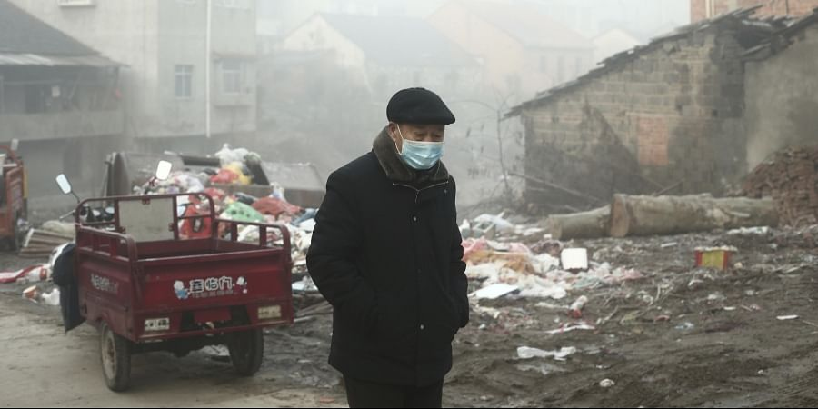 In this Jan. 28, 2020 photo, a man wearing a face mask walks through a village in Jianli county in central China's Hubei Province, the province at the center of a virus outbreak. (Photo   AP)