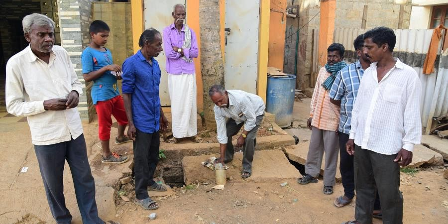 Narayanswamy, a manual scavenger, along with his fellow colleague, shows a pit which needs to be cleaned manually