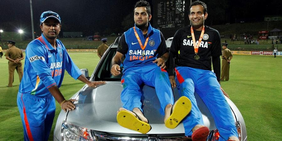 Indian cricketer Virat Kohli pose with the SUV that he won as the man-of the series with teammates Irfan Pathan and Pragyan Ojha after India beat Sri Lanka in the five- match ODI series in Pallekele, Sri Lanka.