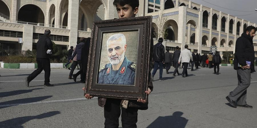 A boy carries a portrait of Iranian Revolutionary Guard Gen. Qassem Soleimani, who was killed in a U.S. airstrike in Iraq, prior to the Friday prayers in Tehran, Iran, Friday Jan. 3, 2020.