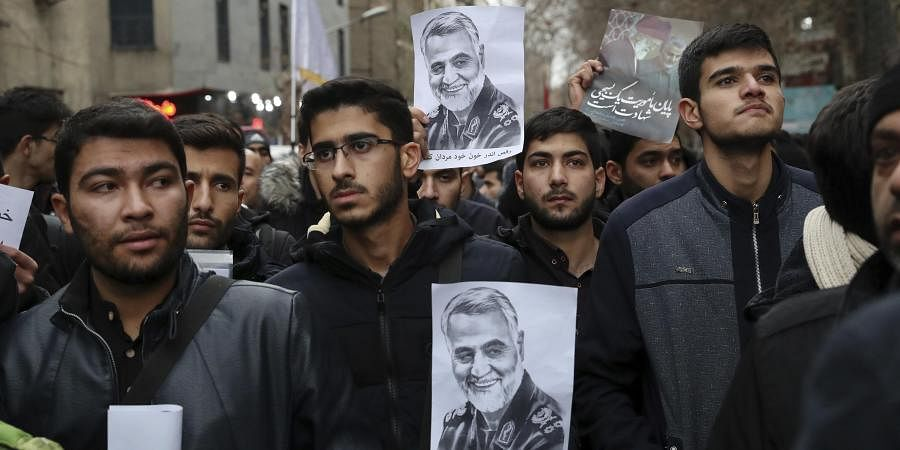 Protesters hold up posters of General Qassem Soleimani while mourning during a demonstration over the US airstrike in Iraq that killed the top army officer in Tehran