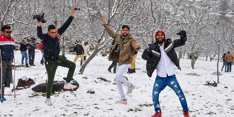 Tourists play with snow after fresh snowfall near Palchan in Kullu district