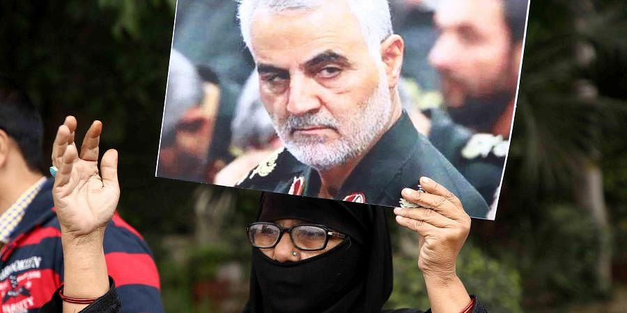 An Indian woman holding placards protest against American President Donald Trump against the killing of Iranian military commander Qasem Soleimani near the US Embassy in New Delhi on Tuesday.