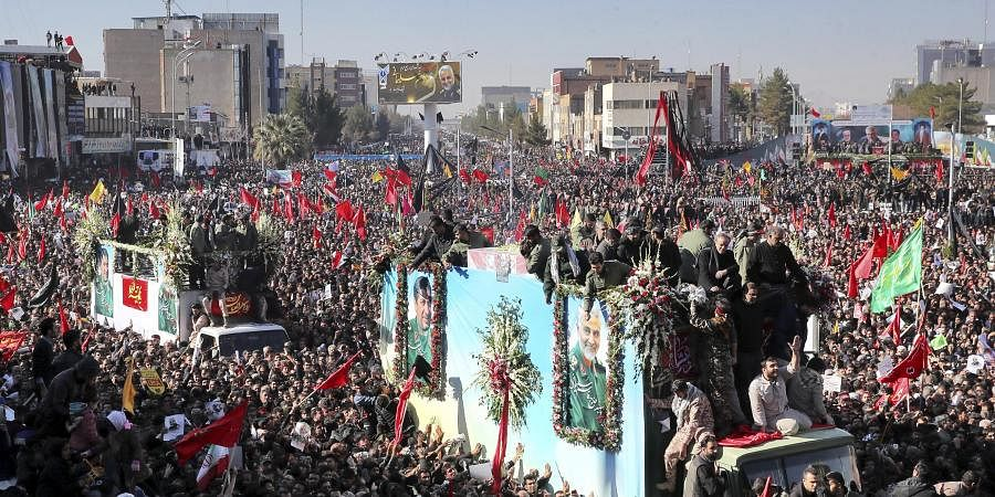 Coffins of General Qassem Soleimani and others who were killed in Iraq by a US drone strike, are carried on a truck surrounded by mourners during a funeral procession in Kerman on Tuesday.