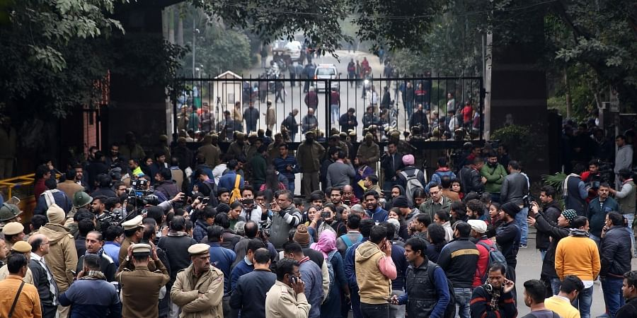 Police personnel stand guard as students and media gather before the main gate of the Jawaharlal Nehru University JNU.
