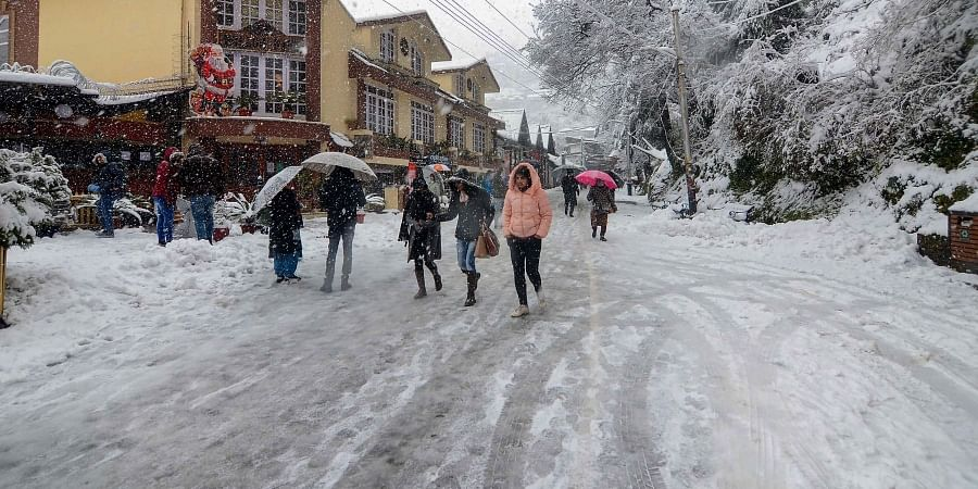 People walk on a snow covered road amid heavy snowfall in Shimla on Wednesday Jan. 8 2020. (Photo   PTI)
