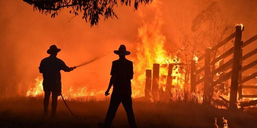 Residents defend a property from a bushfire at Hillsville near Taree, 350km north of Sydney. (Photo   AFP)