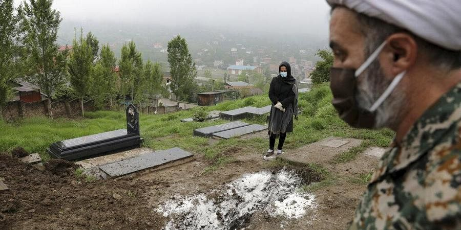 A woman wearing mask and gloves, prays at the grave of her mother who died from COVID-19. (Photo | AP)