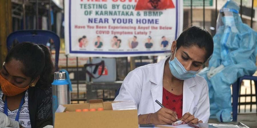 Health staffers at a fever clinic take down details of people for testing in Bengaluru