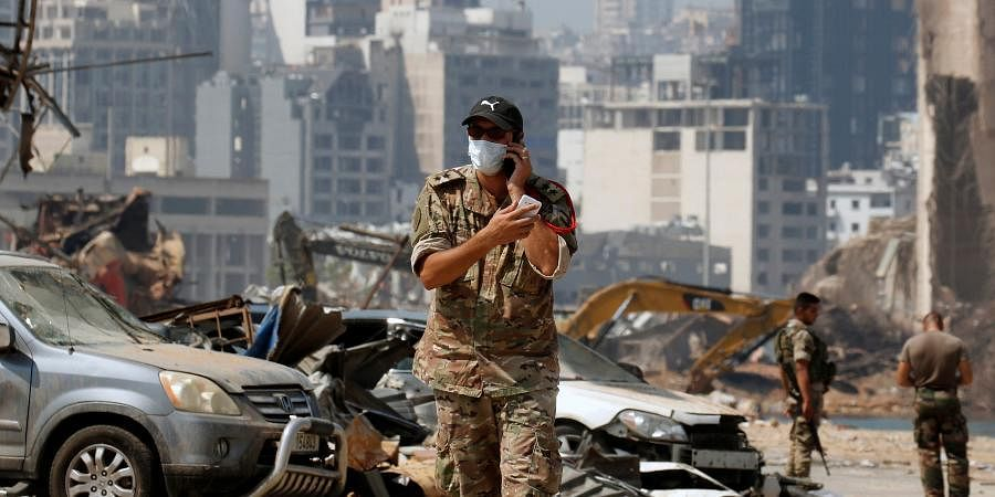 A Lebanese soldier uses his phone at the damaged site of the massive blast in Beirut's port area, in Beirut.