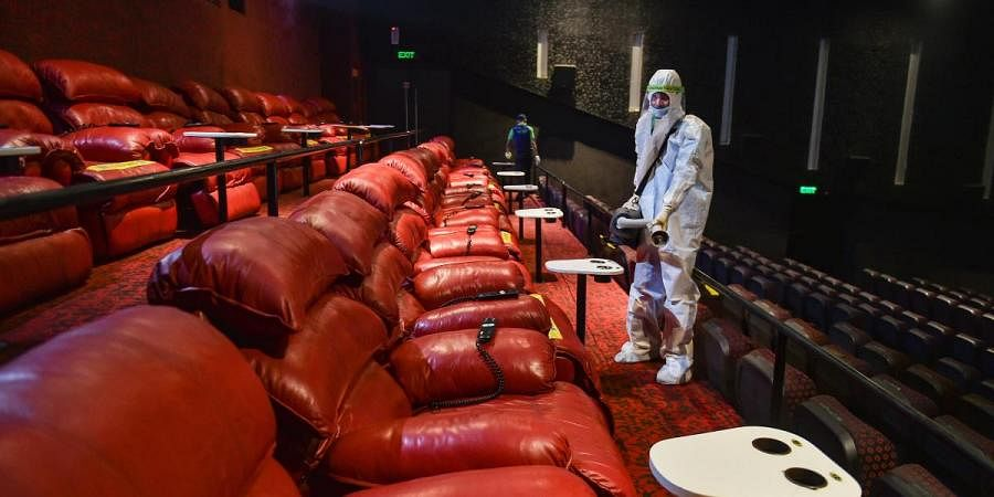 A worker wearing PPE kit sanitises a cinema hall as multiplexes prepare to re-open from October 15