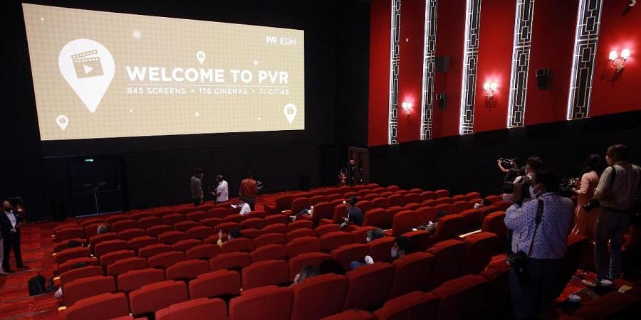 A worker sanitises inside a theatre hall at PVR ICON ahead of the scheduled reopening of cinema theatres on October 15 in New Delhi