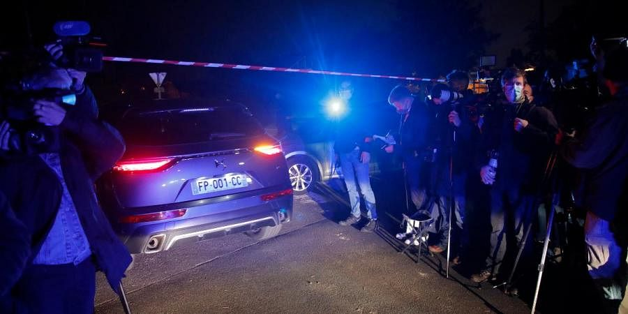 A police car enters the perimeter after a history teacher who opened a discussion with students on caricatures of Islam's Prophet Muhammad was decapitated