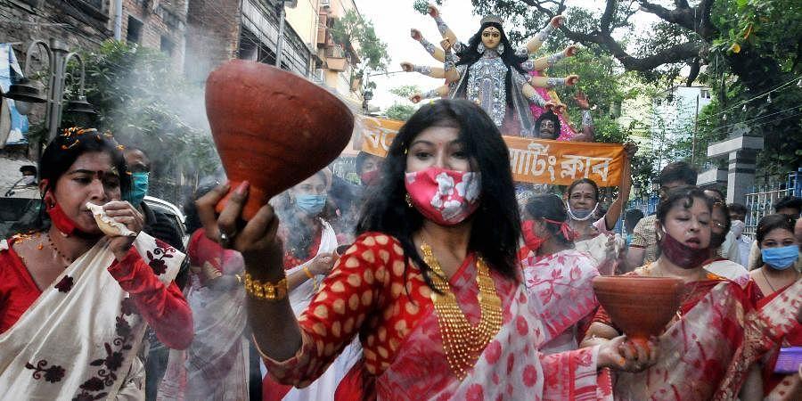 Women perform 'Dhunachi' dance on the arrival procession of Goddess Durga idol at their community puja pandal ahead of 'Durga Puja' festival amid coronavirus pandemic in Kolkata.