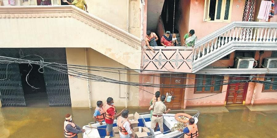 TRS Corporator Vijaya Reddy distributes food packets to residents, who have been marooned off in the floods at Khairatabad, on Thursday