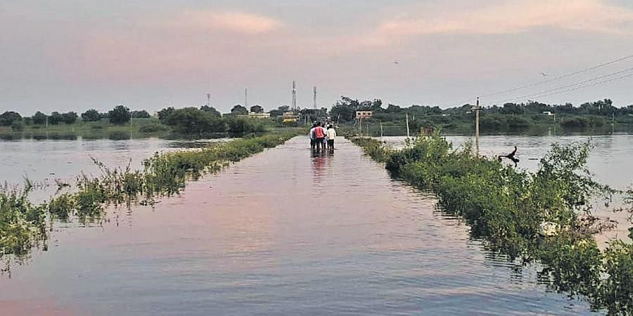 Villagers wade through a road submerged in rain water at Bandarwad in Kalaburgi district on Saturday. Heavy rain has been lashing the district for the past few days