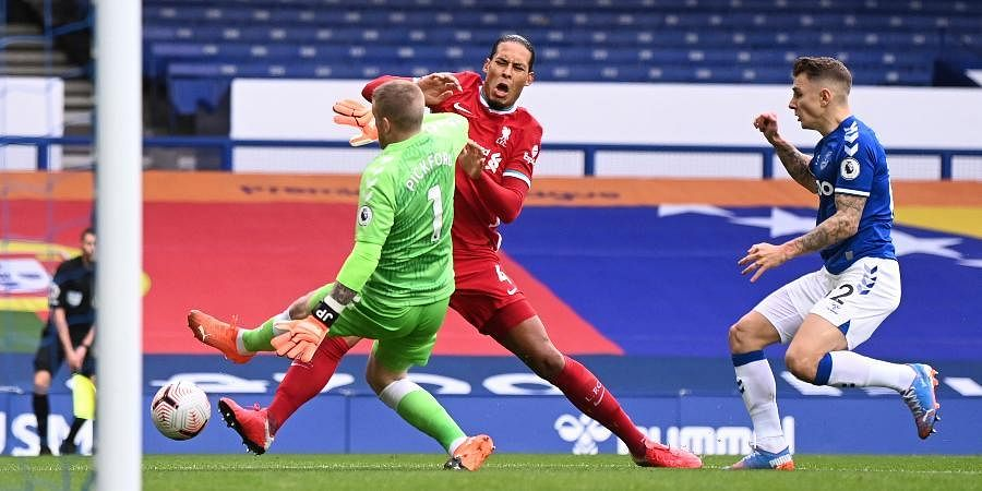 Liverpool's Virgil van Dijk (C)is tackled and injured by Everton's goalkeeper Jordan Pickford (L)causing him to leave the match injured.