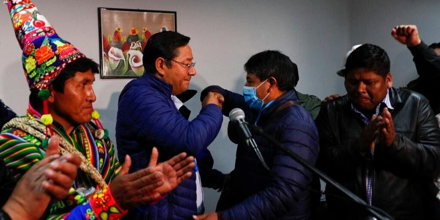 Luis Arce, second left, Bolivian presidential candidate for the Movement Towards Socialism Party, MAS, and running mate David Choquehuanca, second right, shake hands during a press conference after general elections in La Paz, Bolivia