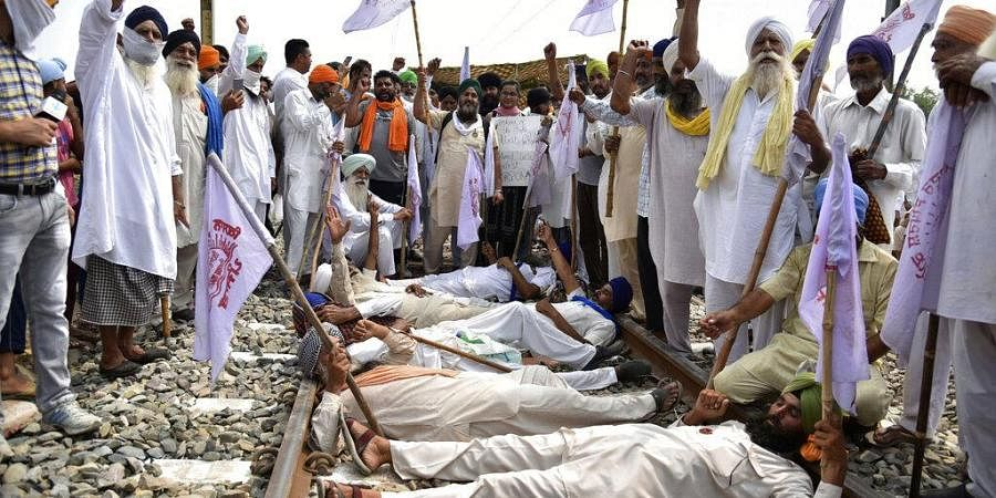 Farmers shout slogans as they block a railway track protesting against the new farm bills, at Devi Dass Pura village, about 20 kilometers from Amritsar, India, Thursday, Sept. 24, 2020.
