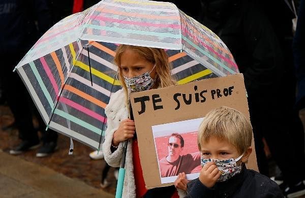 A child holds up a a poster of Samuel Paty as people gather on Republique square in Lille, northern France.