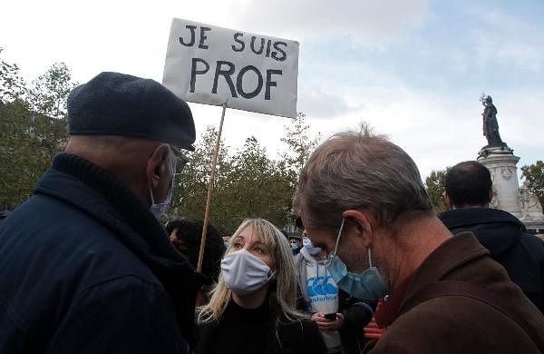 People gather on Republique square, one with a poster reading 'I am a teacher' during a demonstration in Paris.