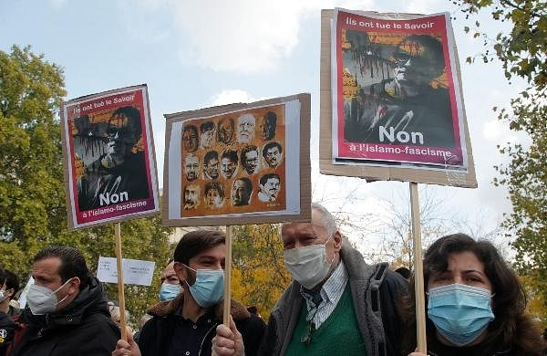 People gather with portrait of slain teacher Samuel Paty during a demonstration in Paris.