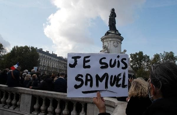 People gather on Republique square, one with a poster reading 'I am Samuel' for a demonstration in Paris.