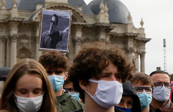 A portrait of Samuel Paty is held up as people gather on Republique square in Lille, northern France.