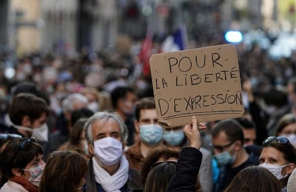 A person holds up a banner that reads: 'For the freedom of speech', during a demonstration in Lyon, central France.