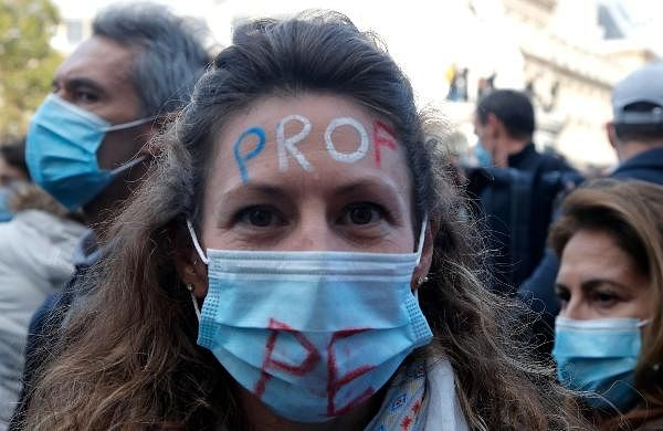 A teacher has her forehead painted with the word Teacher during a demonstration in Paris.