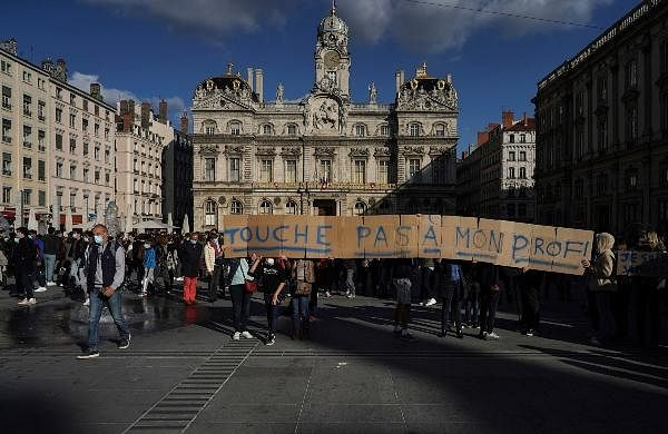 People hold a banner that reads: 'Don't touch my teacher', in Lyon, central France.