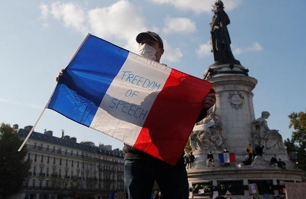 A demonstrator holds a French flag with the slogan 'Freedom of Speech' during a demonstration in Paris.