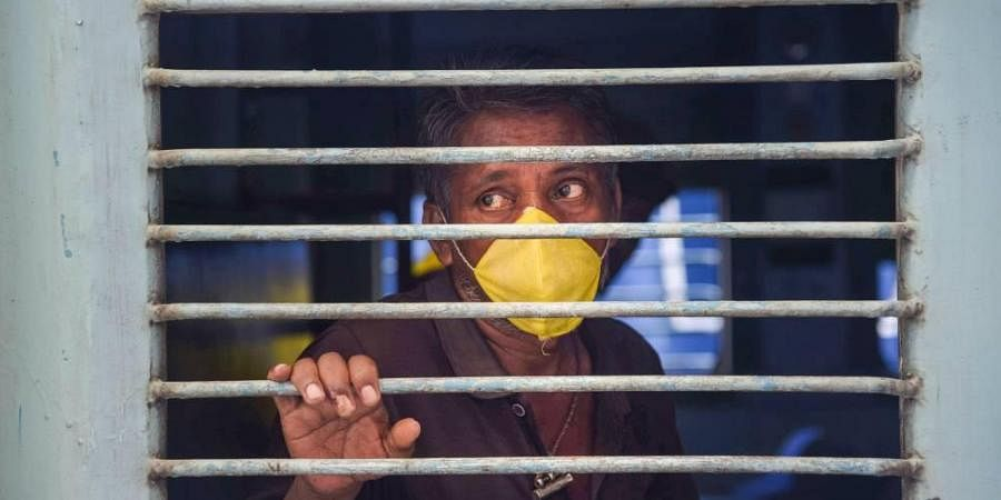 A migrant looks through a window during his departure for Odisha by 'Shramik Special' train at Panvel Railway Station amid the ongoing COVID-19 nationwide lockdown in Navi Mumbai