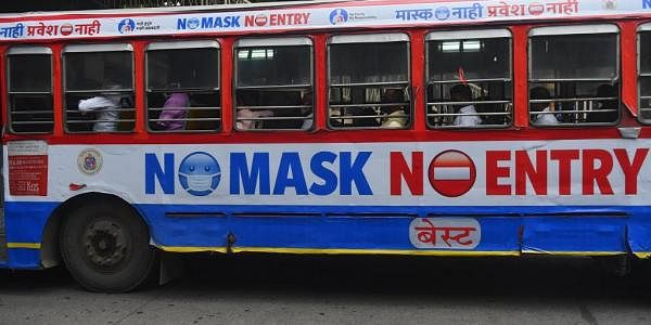 Passengers travel in a bus with a precautionary message pasted against the spread of Covid-19 coronavirus. (Photo| AFP)