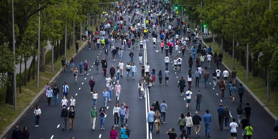 People walk along Paseo de la Castellana after the lockdown measures imposed by the government due to coronavirus in Madrid, Spain, Saturday, May 9, 2020. (Photo | AP)