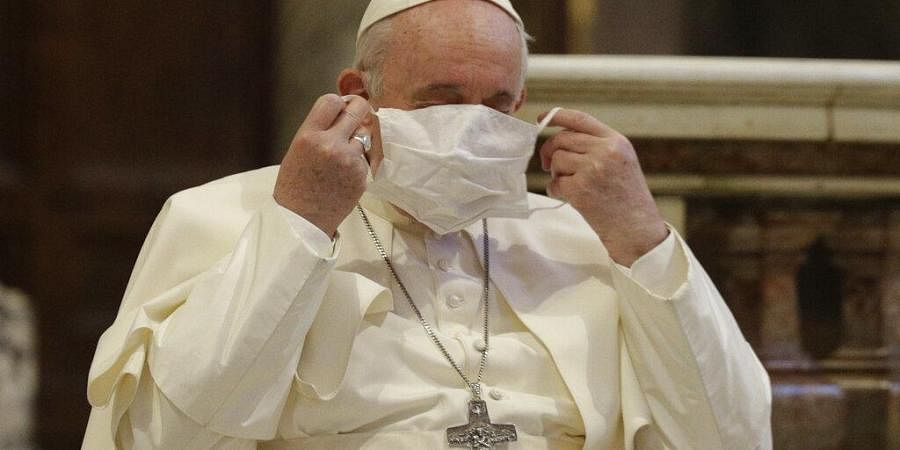 Pope Francis puts on his face mask as he attends an inter-religious ceremony for peace in the Basilica of Santa Maria in Aracoeli, in Rome.