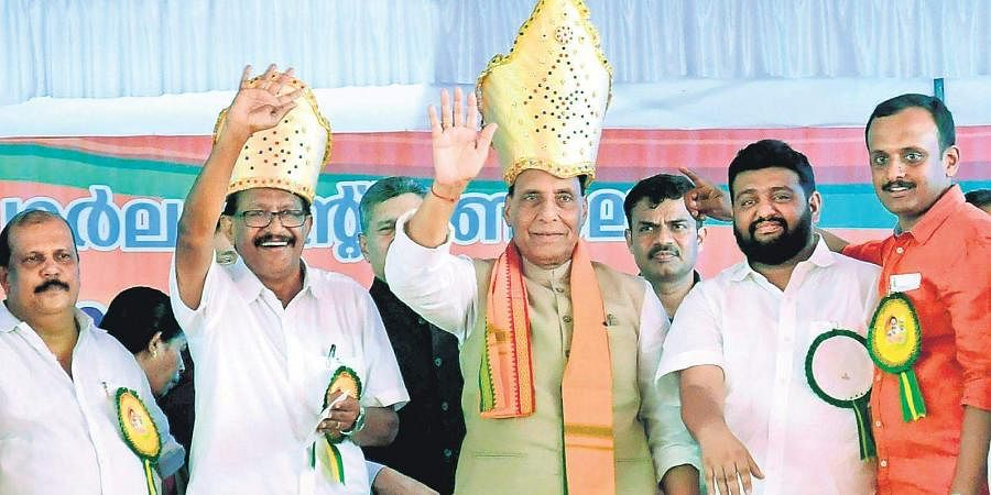 Union Home Minister Rajnath Singh and NDA candidate P C Thomas wave at the audience during a poll-related meeting held at Nagambadom ground in Kottayam on Saturday. Kerala Janapkasham leader PC George is seen
